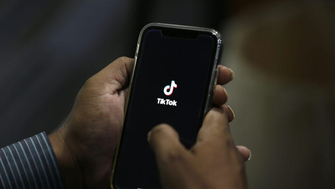 FILE - In this July 21, 2020 file photo, a man opens social media app 'TikTok' on his cell phone, in Islamabad, Pakistan. The owner of TikTok has chosen Oracle over Microsoft as the American tech partner that could help keep the popular video-sharing app running in the U.S., according to a source familiar with the deal who was not authorized to speak publicly about it.