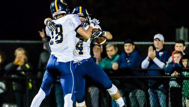 Kade Preston ,left, of DeWitt celebrates with teammate David Locher after Locher ran for a touchdown to give DeWitt an 18-7 lead over St. Johns midway through the 3rd quarter of their game Friday October 7, 2016 in St. Johns.  KEVIN W. FOWLER PHOTO