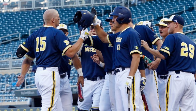 Michigan's Kendall Patrick, left, is greeted by teammates after his solo home run on May 21, 2015.