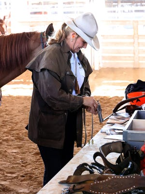 Kim Redo of Mountainburg loads one of her two .45 caliber pistols for her ride in the U.S. Mounted Shooting event, Saturday, Oct. 31, at Kay Rodgers Park. Cowboy mounted shooting is a competitive equestrian sport involving the riding of a horse to negotiate a shooting pattern. Modern events use blank ammunition instead of live rounds, certified to break a target.