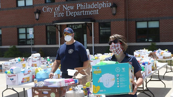 New Philadelphia firefighter Nick McCoy and administrative staff member Denise Phillips work at distributing household items Wednesday in front of the station for the fire department's Compassion Station project. It is part of the department's New Philadelphia CARES (Community Access, Resource, Education and Solutions) program. CARES is designed to improve the quality of life for the city's more vulnerable residents while hopefully reducing the number of unnecessary EMS runs. It is paid for through a grant from Access Tusc.