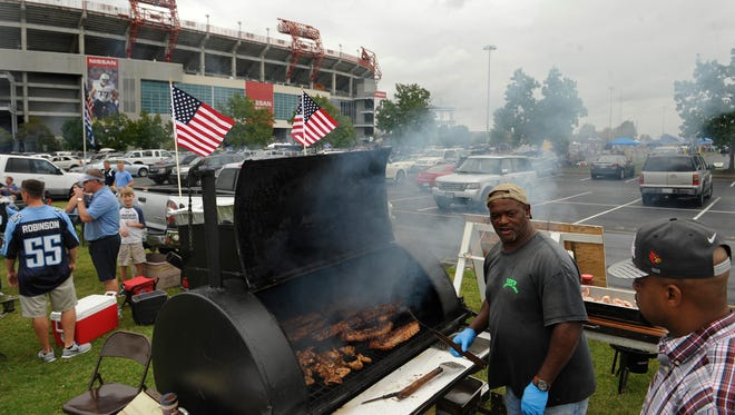 Coy Edmonds, left, talks with son-in-law Cameron Osborne as they grill outside Nissan Stadium on Sunday in Nashville. They were cooking ribs, chicken, Polish sausage, hamburgers and hot dogs.
