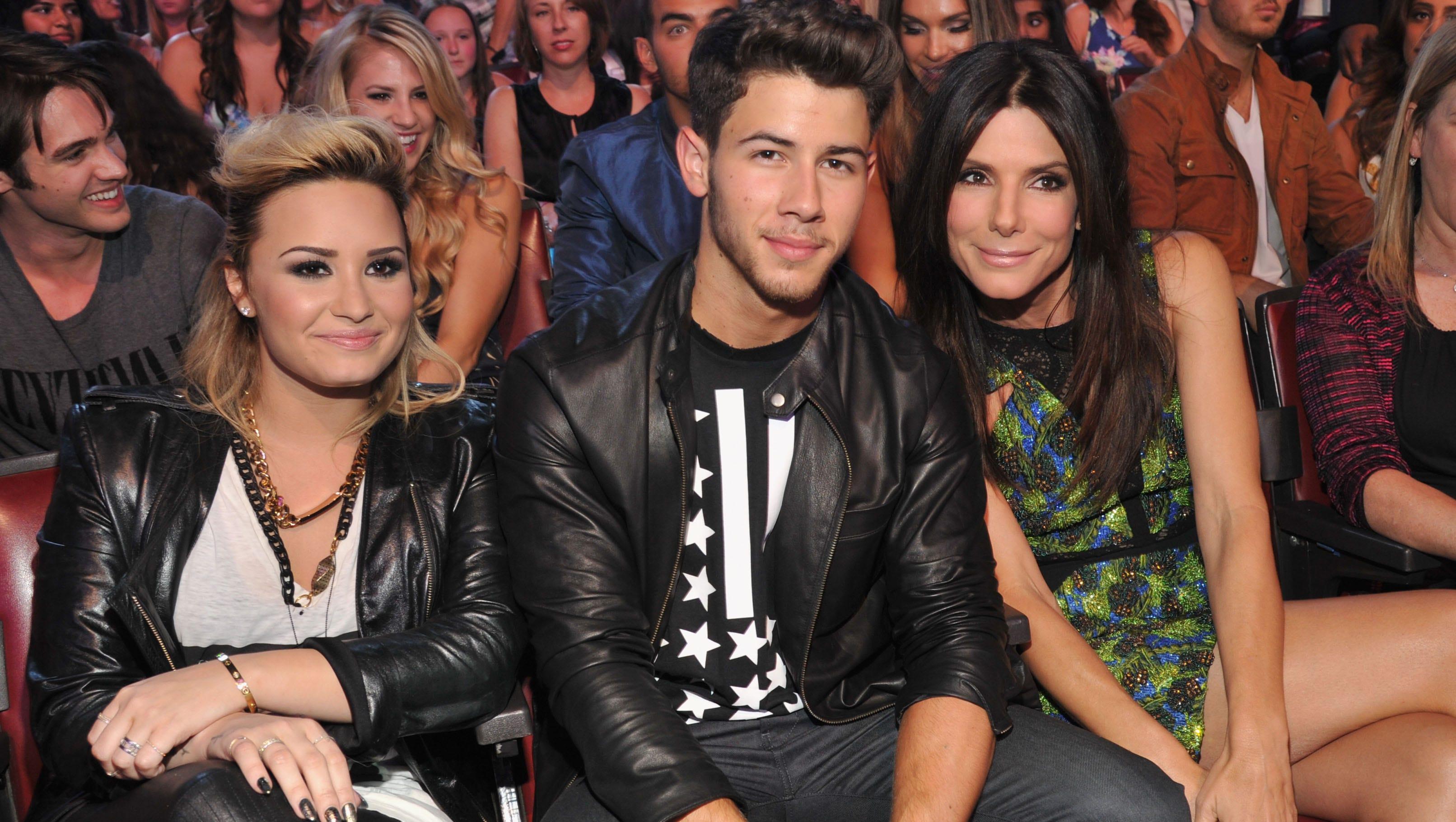 Musicians Demi Lovato, Nick Jonas, and actress Sandra Bullock  enjoy the show.