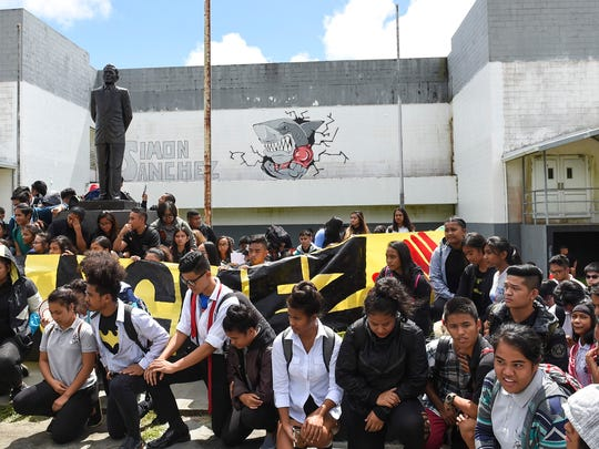 Simon Sanchez High School students take a knee during a protest on their campus in Yigo on Oct. 30, 2017. The protest, organized by Sanchez students Nestor Casin, 17, and Hacie San Jose, 16, calls for urgency on the rebuilding of their dilapidated campus building.