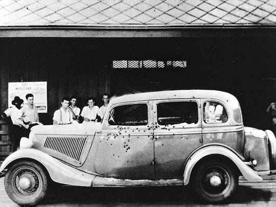 "Bonnie and Clyde's ""death car"" on display somewhere in the United States in the late 1930s, early 1940s. One estimate puts the number of bullets that were fired into the car at 106."