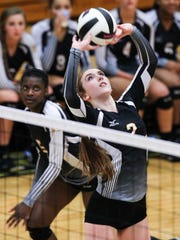 T.L. Hanna's Gabby Easton sets a ball for teammate Jodorrian Taylor against Rock Hill during the first set of Class AAAAA state playoff round two action at T.L. Hanna High School in Anderson.