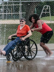 Wandasia Wilson and Kimberly Nash have fun playing on the splash pad at Boro Beach during National Night Out.