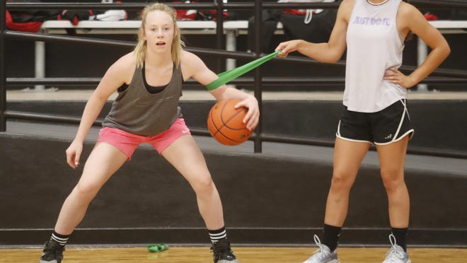 New Home High School varsity basketball players Addy Burns (left) and Morgan Addison practice ball skills during the first day of the UIL-approved, sport-specific instruction and summer strength and conditioning workouts on Monday.