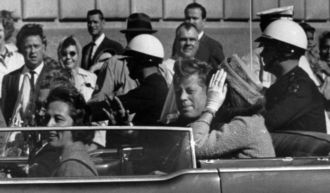 President John F. Kennedy, waving, rides in a motorcade with first lady Jacqueline Kennedy before he was shot and killed in Dallas.