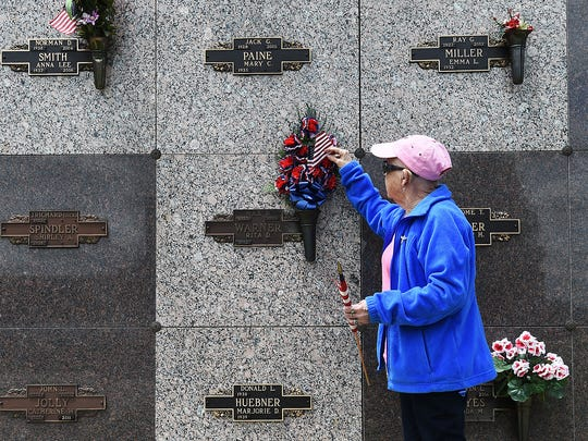 Rita Warner arranges flowers at the grave site of her husband, Max, who served his country in Korea.