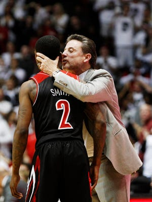Louisville Cardinals head coach Rick Pitino talks to guard Russ Smith (2) near the end of the second half against the Cincinnati Bearcats at FifthThird Arena. Louisville defeated Cincinnati 58-57.