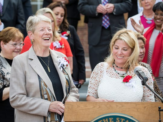 Sen. Karen Peterson, D-Stanton, laughs as House Majority Leader Valeria Longhurst, D-Bear, thanks her at a bill signing ceremony on the steps of Legislative Hall in Dover on Thursday evening. The session ended in a marathon all-night series of bill approvals.