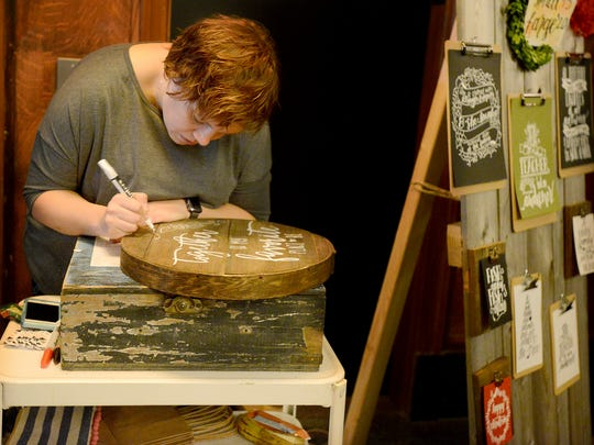 Amanda Larsen Wells makes handmade signs during the Yule Tide Pop-up Shop at the New Southern on Saturday.