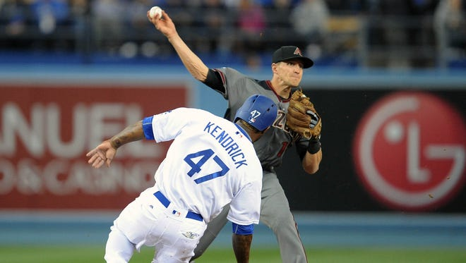 April 14, 2016; Los Angeles; Los Angeles Dodgers third baseman Howie Kendrick (47) is out at second on a double play as Arizona Diamondbacks shortstop Nick Ahmed (13) throws in the second inning at Dodger Stadium.