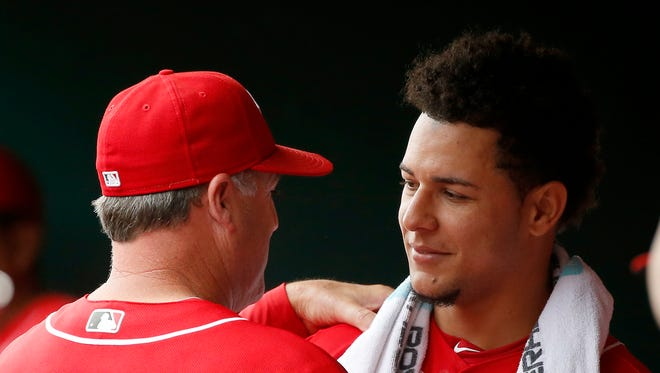Cincinnati Reds manager Bryan Price (38) congratulates starting pitcher Luis Castillo (58) in the dugout after the top of the eighth inning during the game between the Cincinnati Reds and the Milwaukee Brewers at Great American Ball Park on Sept. 6.