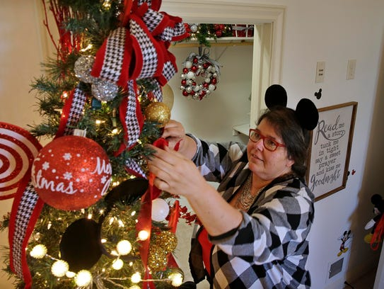 Liz Schutz puts finishing touches on a tree in the