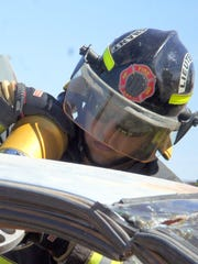 Lt. Julian Hernandez, of thye Deming Fire Department, works on a vehicle with an power tool to extricate a passenger dummy during training on Monday. The DFD will complete 12 days of emergency extricating procedures to achieve international accreditation.