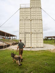Brian Jones, chief executive officer, and his dog Sarge walk toward their sniper and rapelling building out by the shooting range.