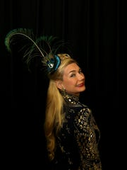 Ava Sand of Royal Oak, Michigan wearing an Emilio Pucci dress and a fascinator peacock feather poses before heading into the 2017 North American International Auto Show Charity Preview at Cobo Center in Detroit on Friday, Jan. 13, 2017.