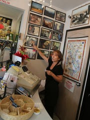 Pina Simone, owner of the Pasta House in Windsor's Little Italy, points to family photographs from Italy's Abruzzo region.
