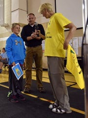Yell and Tell founder Jean Davidson of Milwaukee talks to Sunrise Elementary School student Owen Pichette, the recipient of the program's Squawk Hero award. In background is the school's Dean of Students Brian O'Handley.
