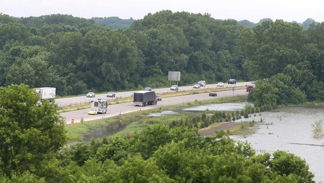 Traffic drives along Interstate 80 near Van Meter as water from the Raccoon River inches close to the shoulder of the interstate on Friday, June 26, 2015.