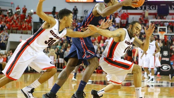 Mississippi orward Aaron Jones comes up with a loose ball for a steal between Georgia guard J.J. Frazier, left, and forward Cameron Forte during the first half of an NCAA college basketball game Tuesday, Jan. 20, 2015, in Athens, Gal. (AP Photo/Atlanta Journal Constitution, Curtis Compton)