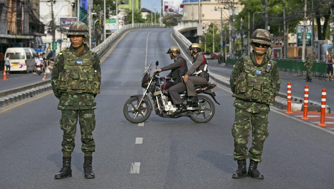 A  motorbike crosses as Thai police take over the streets surrounding the Victory Monument on May 30, 2014 in Bangkok, Thailand.