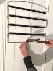 It's easy to attach a swivel arm pant hanger to the wall.