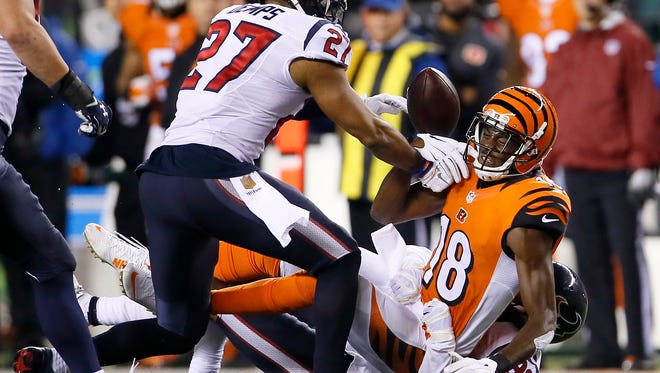 Cincinnati Bengals wide receiver A.J. Green (18) fumbles after Houston Texans strong safety Quintin Demps (27) knocks it of his hands in the fourth quarter during the Week 10 NFL football game between the Houston Texans and the Cincinnati Bengals, Monday, Nov. 16, 2015, at Paul Brown Stadium in Cincinnati.