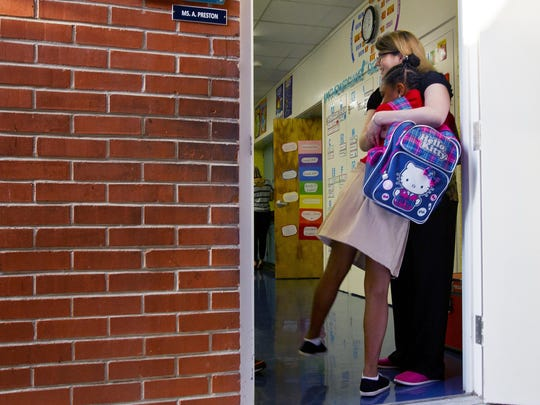 Amanda Preston, a new teacher at Franklin Park Elementary school in Fort Myers, welcomes a student during the start of school Monday morning.
