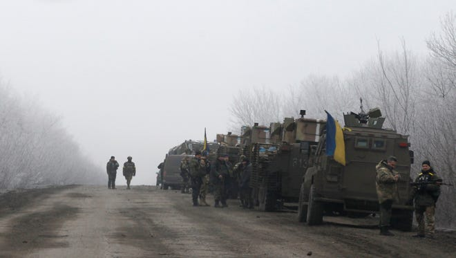 Ukrainian military convoy stop on the road between the towns of Dabeltseve and Artemivsk, Ukraine, Saturday, Feb. 14, 2015.