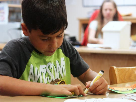 Jose Jimenez Jr., 8 years old, works on coloring a leprechaun during the Alamogordo Public Library's 116th birthday party on Saturday afternoon.