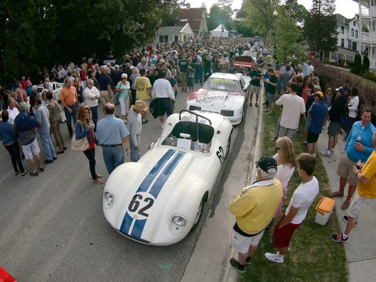 A LIster Jaguar leads a line of cars at the vintage