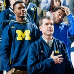 Michigan football early commit Brian Cole, left, stand behind new head coach Jim Harbaugh, bottom, for the national anthem before an NCAA college basketball game against Northwestern at Crisler Center in Ann Arbor, Mich., Saturday, Jan. 17, 2015.
