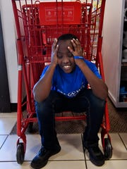"Dauphin Ineza, 9, found a place to rest as he waited for his family to check out at J.C. Penney's Saturday. ""I just needed a place to sit,"" he said, wearily. Dauphin's sister Mutoni Jolie was granted a shopping spree by the Make-A-Wish Foundation."