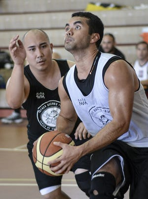Dean Manglona of team '01/03 drives baseline past an '00/02 defender at a Father Duenas Alumni Association Basketball Tournament playoff game at the FD Jungle on June 20. Manglona rallied his team from a 31-18 halftime defecit to win 42-35.
