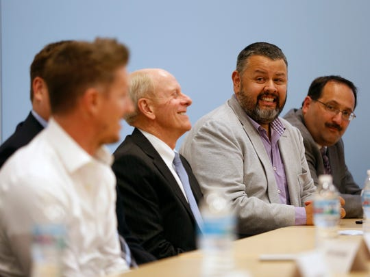 """Gilbert Vicario, senior curator at the Des Moines Art Center (second from right), smiles as Dr. Nate Noble with Blank Children's Hospital introduces himself Wednesday, May 13, 2015, at the start of the """"15 People to Watch in 2015"""" panel discussion in Des Moines."""