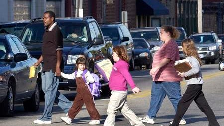 Students and parents cross Pike St from John G. Carlisle Elementary School in Covington, KY at the end of a school day. The school is closed Tuesday, Sept. 23, 2014, due to a water outage.