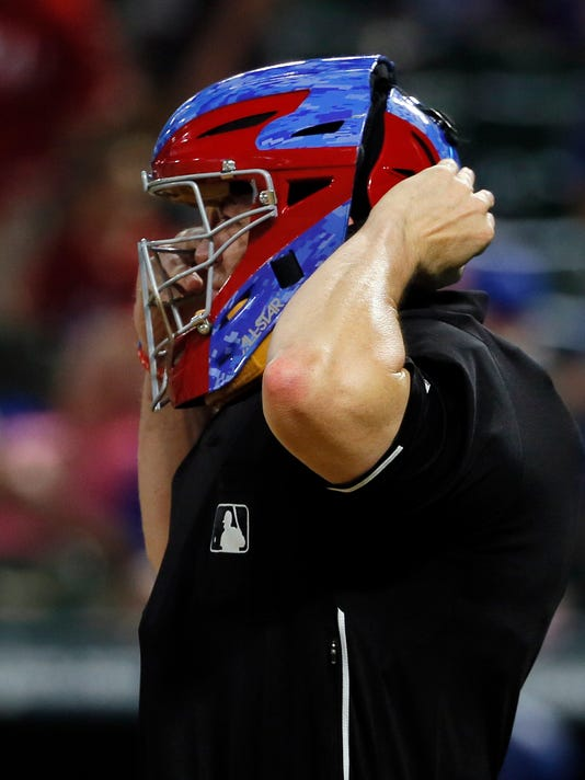 Home plate umpire Carlos Torres adjust his mask during the seventh inning of a baseball game between the Houston Astros and Texas Rangers on Tuesday, Sept. 26, 2017, in Arlington, Texas. Torres wore a Rangers mask during the game. (AP Photo/Tony Gutierrez)