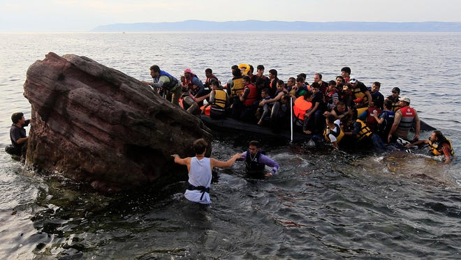 Refugees from Syria arrive on a dinghy after crossing from Turkey at the coast of Mytilini, Lesvos island, Greece. Some 3,000 refugees disembark daily at the coasts of the island, coming from the Turkish coastline. Most of the refugees want to continue their journey to countries of north and central Europe.