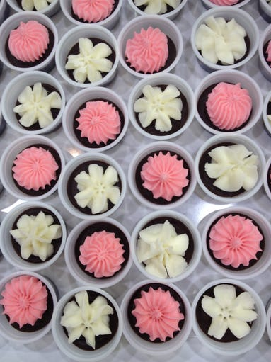 Camille Cappello-Chapman, owner of Queen Choco, created these chocolate truffles topped with pink and white buttercream frosting.