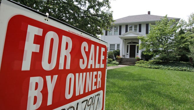 """A """"For Sale by Owner"""" sign rests in front of a house in Cleveland Heights, Ohio."""