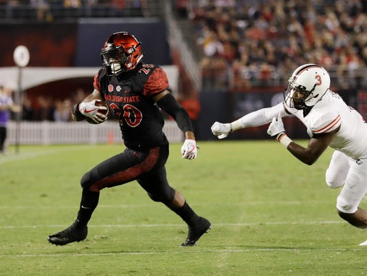 San Diego State running back Rashaad Penny runs past Northern Illinois cornerback Jalen Embry during the second half of an NCAA college football game Saturday, Sept. 30, 2017, in San Diego. (AP Photo/Gregory Bull)