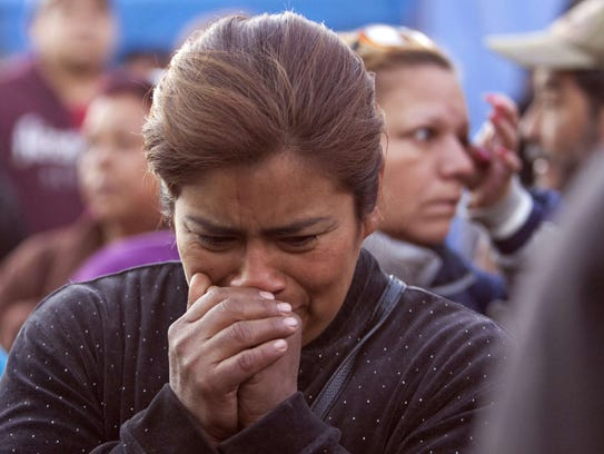 A woman cries as relatives of inmates gather outside