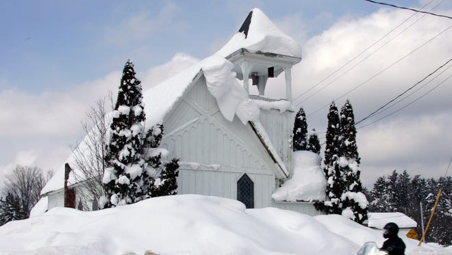 A person riding a snowmobile passes the Wesleyan Church in Redfield, N.Y., Sunday, Feb. 11, 2007.