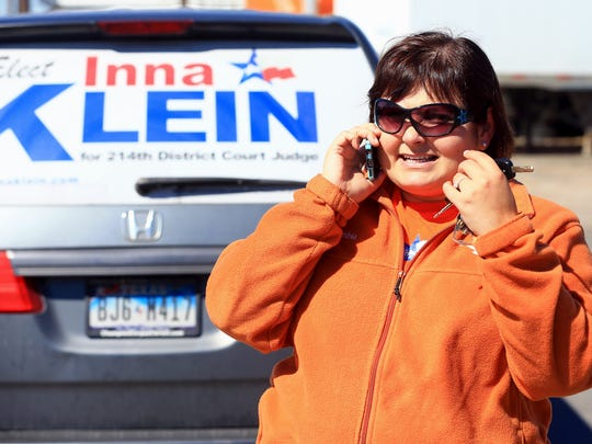 Candidate Inna Klein for the 214th District Court talks on the phone before adjusting her campaign signs Wednesday, Feb. 10, 2016, at Danny's Tire Service in Corpus Christi.