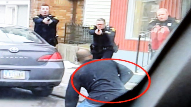 Paul Gaston (circled) had complied with initial commands, but he then reached for a gun when Cincinnati Police officers told him to lie down. Three officers fired nine shots, killing him. This photo was provided by a witness who recorded video on a cell phone. The gun was an Airsoft pistol.