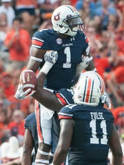 Auburn offensive lineman Avery Young (56) lifts up Auburn wide receiver D'haquille Williams after Williams scores a touchdown against Louisiana Tech.