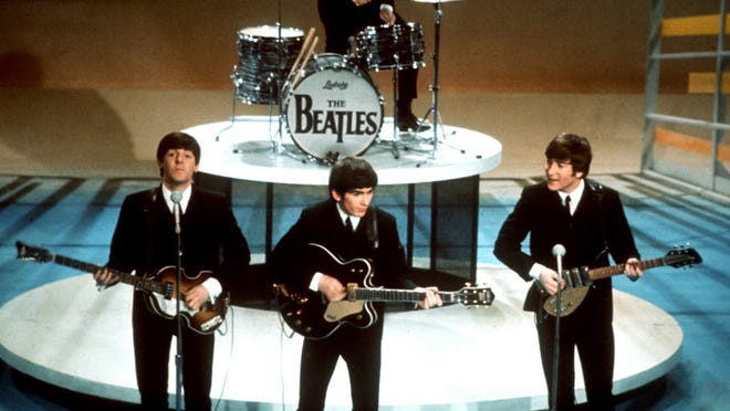 """The Beatles perform on the CBS """"Ed Sullivan Show"""" in New York on Feb. 9, 1964. From left (front) are Paul McCartney, George Harrison and John Lennon. Ringo Starr plays drums."""